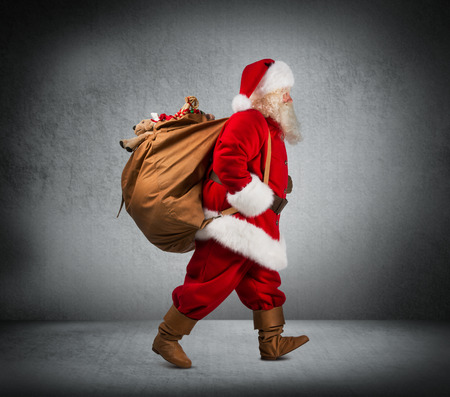 Santa Claus walking with the bag of the presents photo