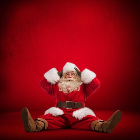 Hilarische en grappige Kerstman zittend op de vloer en kijkt gefrustreerd op een rode achtergrond volledige lengte