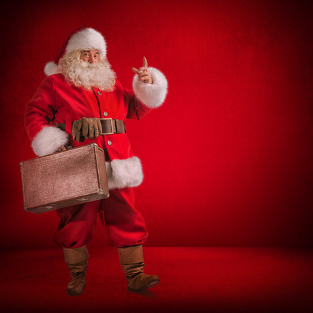 Christmas: Santa Claus Standing With Travel Bag with Gits on red background photo