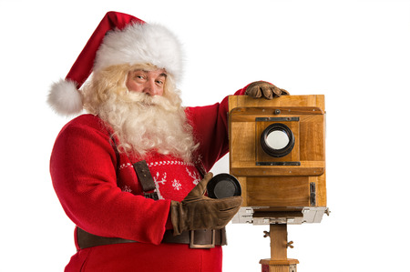 photo studio background: Santa Claus taking picture with old wooden camera Stock Photo