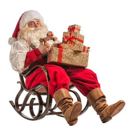 Zitting van de Kerstman in schommelstoel met geschenken op een witte achtergrond Stockfoto