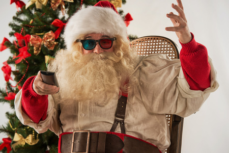 Santa Claus sitting in rocking chair near Christmas Tree at home and watching tv or home theater wearing 3d glasses and holding remote control photo