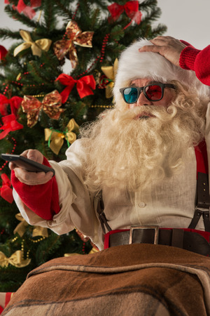christmas movies: Santa Claus sitting in rocking chair near Christmas Tree at home and watching tv or home theater wearing 3d glasses and holding remote control