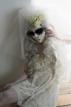 Halloween witch. Beautiful woman wearing santa muerte mask and wedding dress. Dead widow in grief photo
