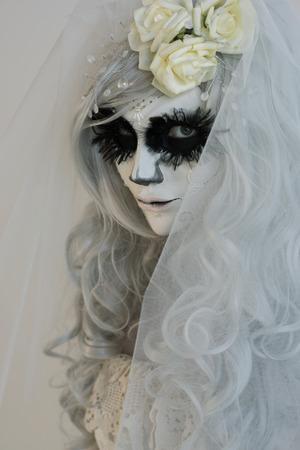 Halloween witch. Beautiful woman wearing santa muerte mask and wedding dress photo