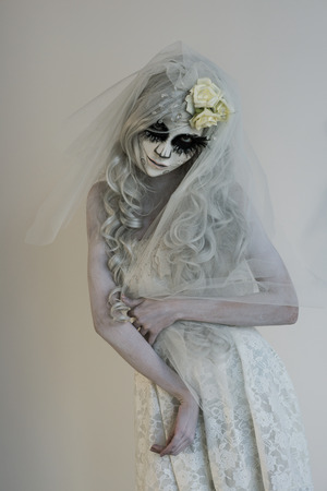 Halloween witch. Beautiful woman wearing santa muerte mask and wedding dress. Dead widow in grief Stock Photo
