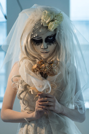 Halloween witch. Beautiful bride woman wearing santa muerte mask and wedding dress holding dead bouquet of roses photo