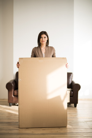 moving box: Cheerful woman holding a cardboard box while moving in new home