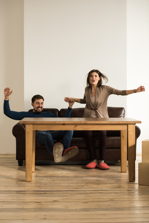 Front view of happy young couple placing sofa and table in living room of new home. Jumping after finished work photo