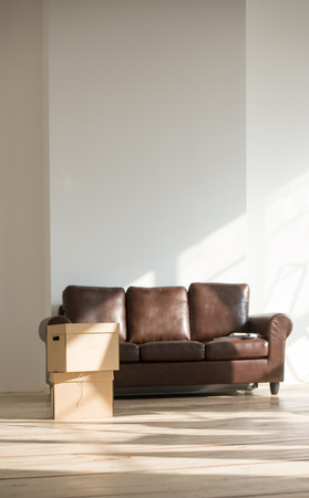 Sofa and cardboard boxes in new home. Moving in and mortgage concept photo
