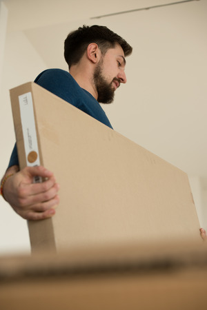 Man carrying stacked boxes on moving day photo
