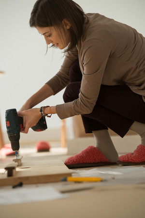self assembly: Woman Putting Together Self Assembly Furniture In New Home