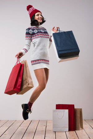 Pretty woman jumping with shopping bags against white wall background, wearing knitted hat and dress photo