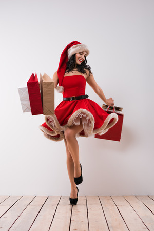 girl in red dress: Pretty woman jumping with shopping bags against white wall background, wearing red Santa Claus hat and dress Stock Photo
