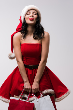 Young beautiful Christmas woman wearing Santa Claus red hat and dress pokes out her tongue photo