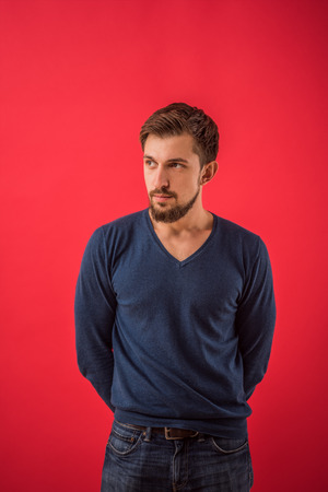 exacting: Serious man looking away standing against red background Stock Photo