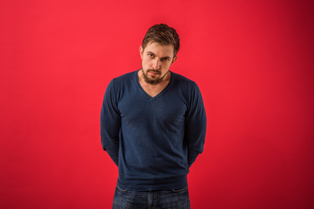 exacting: Serious man looking at camera standing against red background