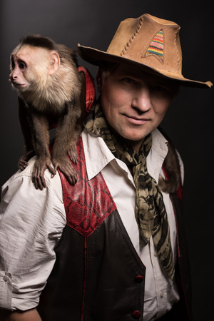 adventurer: Mature man adventurer in costume of traveler with his monkey companion on black background Stock Photo