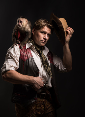 adventurer: Mature man adventurer in costume of traveler with his monkey companion holding old gun on black background Stock Photo