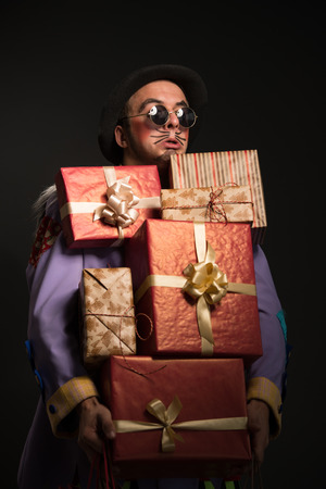 a lot: Man clown carrying a lot of Christmas gifts