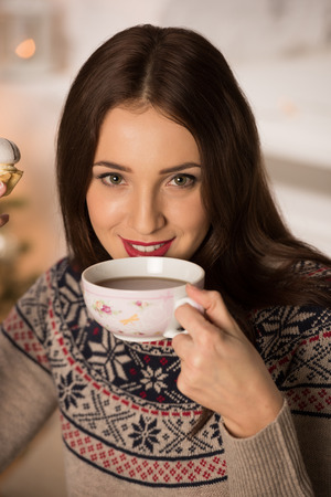 Young woman at home sipping tea from a cup photo