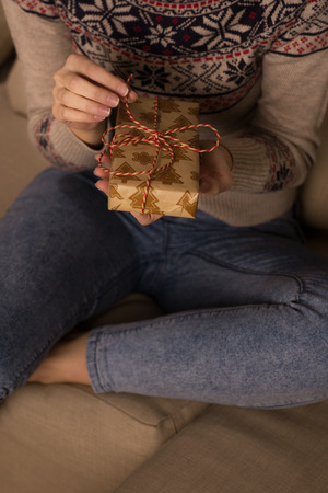 unrecognizable: Unrecognizable woman opening Christmas gift at home