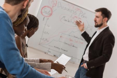 Zakelijke bijeenkomst op kantoor. Knappe man die grafieken op whiteboard aan het team. Multi-etnische groep mensen Stockfoto