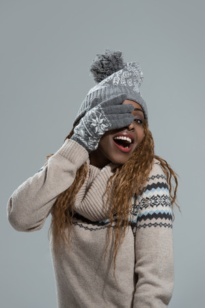 closing eyes: Winter african girl, young beautiful smiling and closing eyes with hands on gray background Stock Photo
