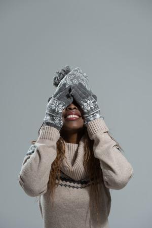 eyes closing: Muchacha del invierno africano, joven y bella sonrisa y cerrando los ojos con las manos sobre fondo gris