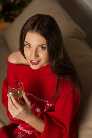 Beautiful young woman wearing Christmas sweater with deers ornament sitting on sofa near Christmas Tree photo