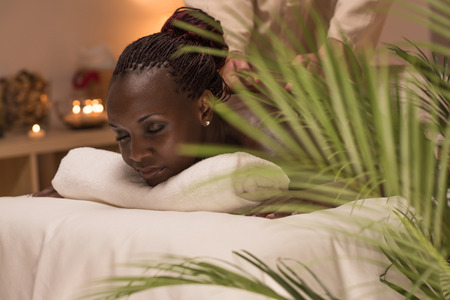 male massage: Masseur doing massage to african woman body in the spa salon. Beauty treatment concept.