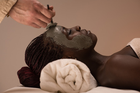 Beautiful african woman having clay facial mask applying by beautician photo