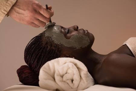 masajes faciales: Hermosa mujer africana con m�scara facial de arcilla aplicar por esteticista