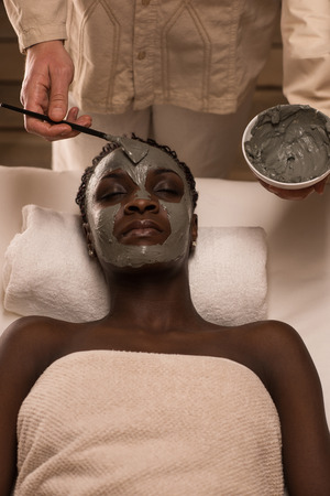 Professional applying mud mask to african woman at spa salon. Top view photo