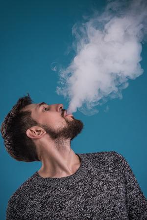 Knappe man vaping tegen blauwe achtergrond