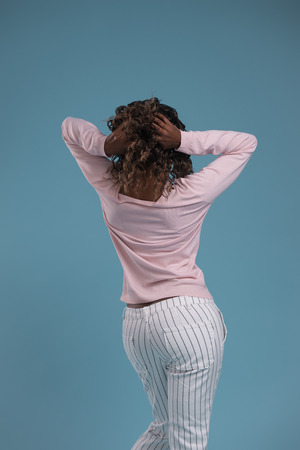 African young woman posing against blue background. Photo from behind