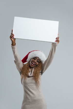 Smiling young african woman in Santa Claus hat holding sign overhead photo