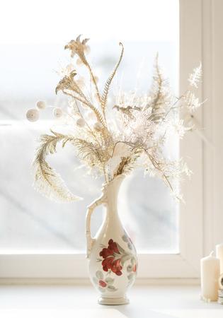 Golden flowers in vintage vase on windowsill photo