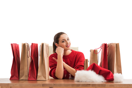 Pretty young Christmas woman sitting at office with shopping bags and laughing photo