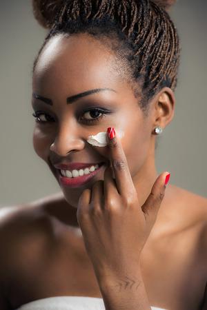 femme noire nue: Beaut� visage de jeune femme afro-am�ricaine � la cr�me cosm�tique sur une joue. concept de soins de la peau. Portrait Gros plan.