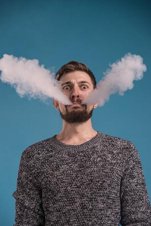Knappe expressieve man vaping tegen blauwe achtergrond