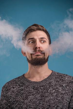 Handsome expressive man vaping against blue background photo