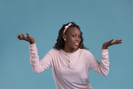 happy young woman: Beautiful African woman making a scale with her arms wide open on blue background