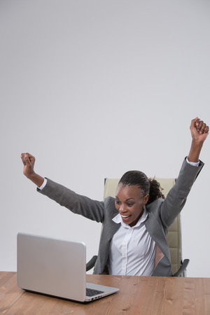 Successful business woman with arms up sitting in front of laptop at office photo