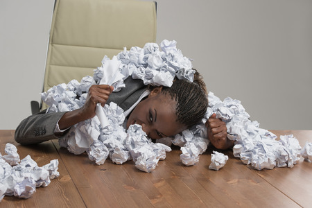 anguished: Young african business woman covered in crumpled papers against gray background