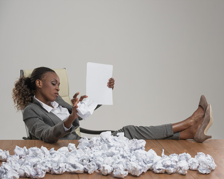 working hours: African business woman looking for workers . She is unhappy with cv of applicants and throwing crumpled papers with resume applications on table