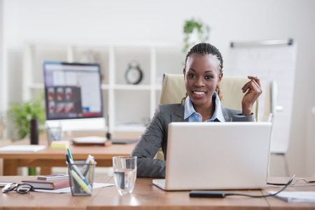 single: Pretty cheerful african businesswoman working with laptop in office and looking at camera