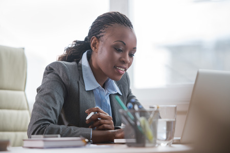 mujeres sentadas: Mujer de negocios bastante africano trabajando en la computadora portátil en la oficina