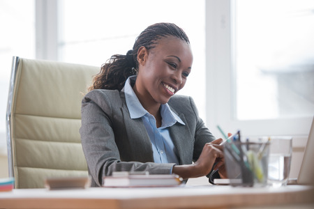 white collar worker: African Business woman working using laptop computer in office Stock Photo