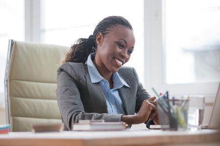 secretaria sexy: Mujer de negocios africano que trabaja usando la computadora port�til en la oficina